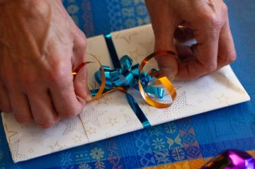 Photo of two older hands tightening a ribbon on a gift cardby Ivan on Unsplash