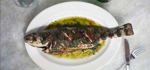 Whole grilled fish on plate